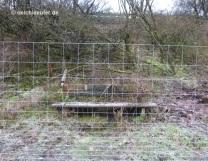 Bank hinter (Zaun-)Gittern